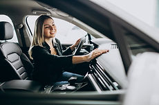 young-woman-testing-car-car-showroom_130
