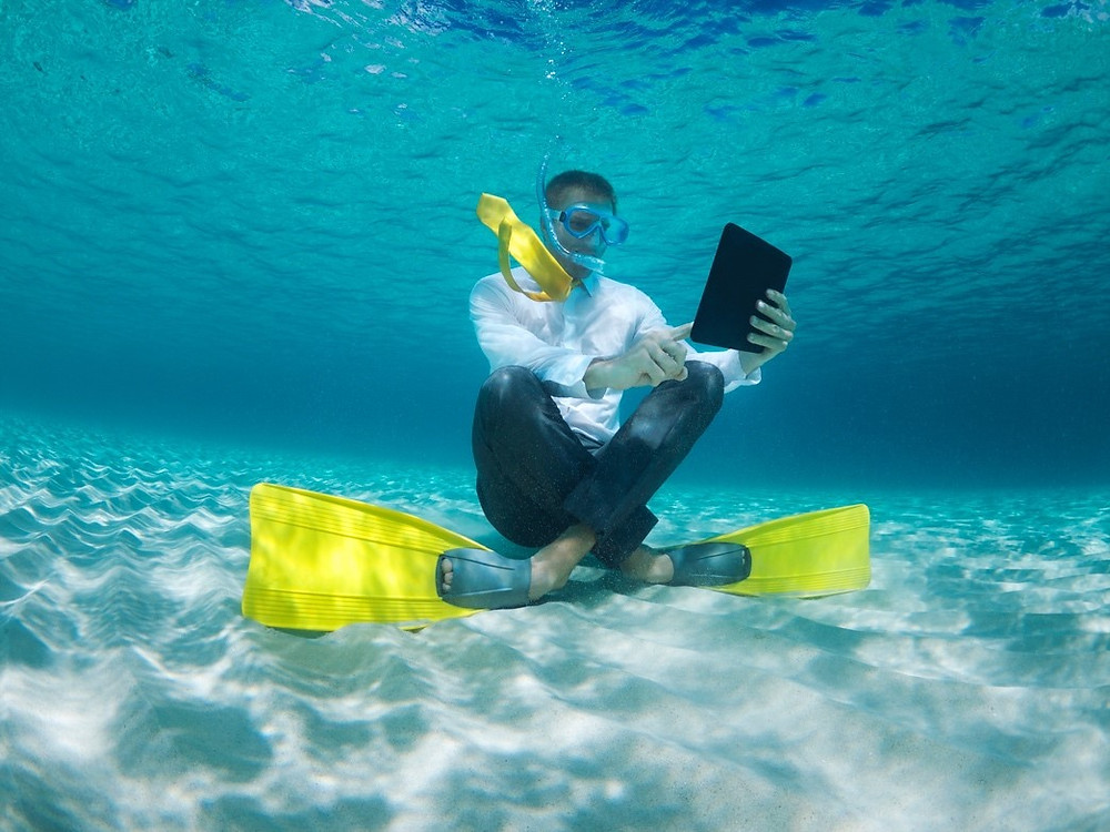 business man under water checking emails while on vacation