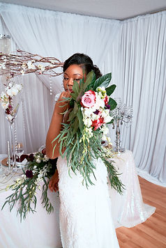 Bride holding bouquet over her shoulder in front of the head table