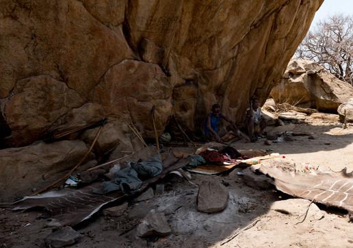 Группа мужчин племени хадза (охотники-собиратели) отдыхает после удачной охоты.