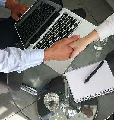 Two people shaking hands over a desk with laptop