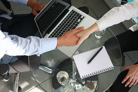 Two people shake hands over a table with a laptop and notebook
