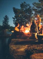 group of people near bonfire near trees