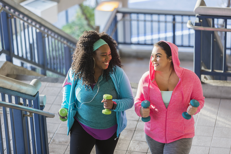 Two-young-women-exercising,-powerwalking-up-stairs-647090176_5760x3840