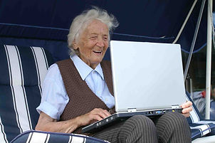 elderly woman laughing with a laptop