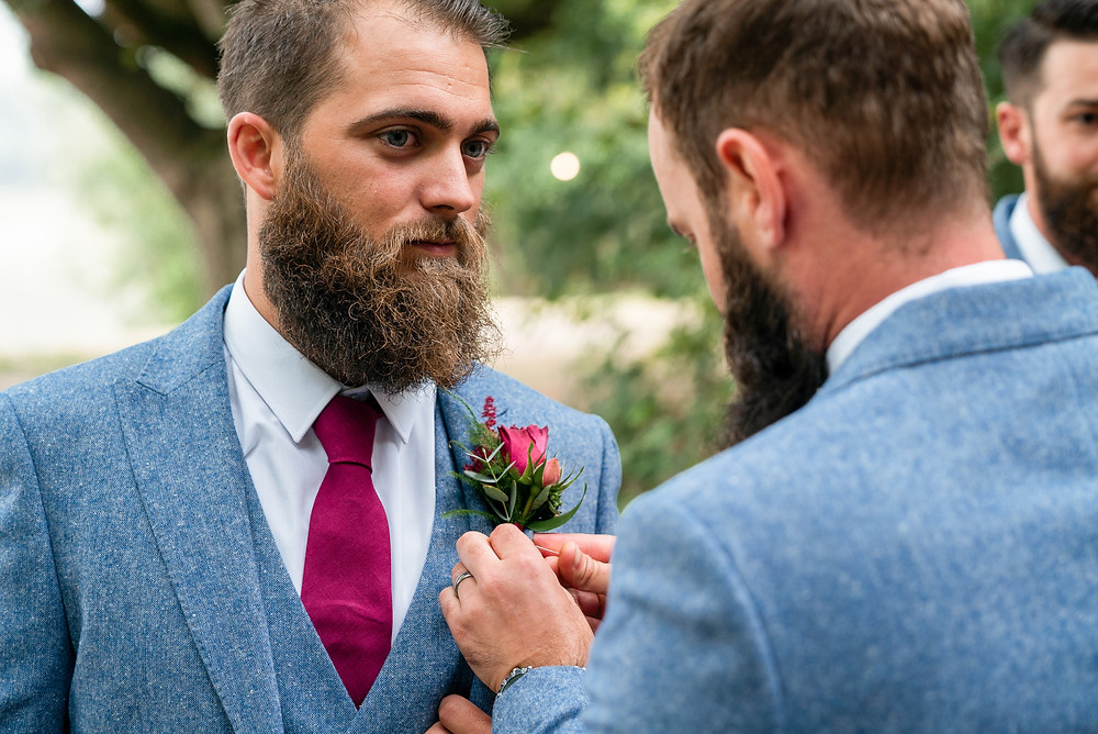 Groomsmen helping Groom with Buttonhole