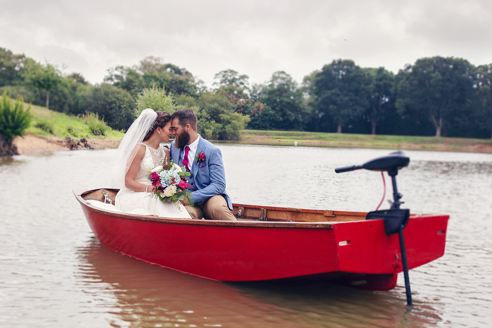 Bride and groom sat together in boat on lake