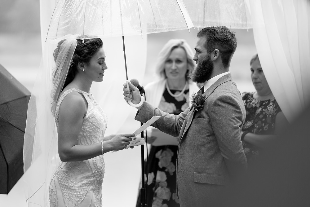 Groom holds umbrella over bride as she reads vows