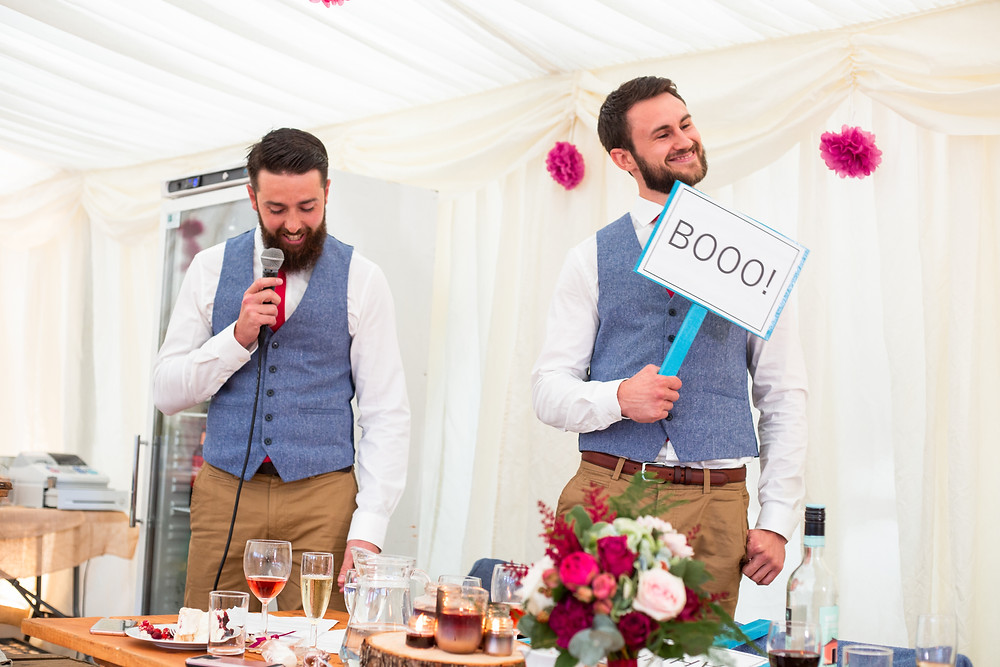 Brides brothers giving speech, booo sign
