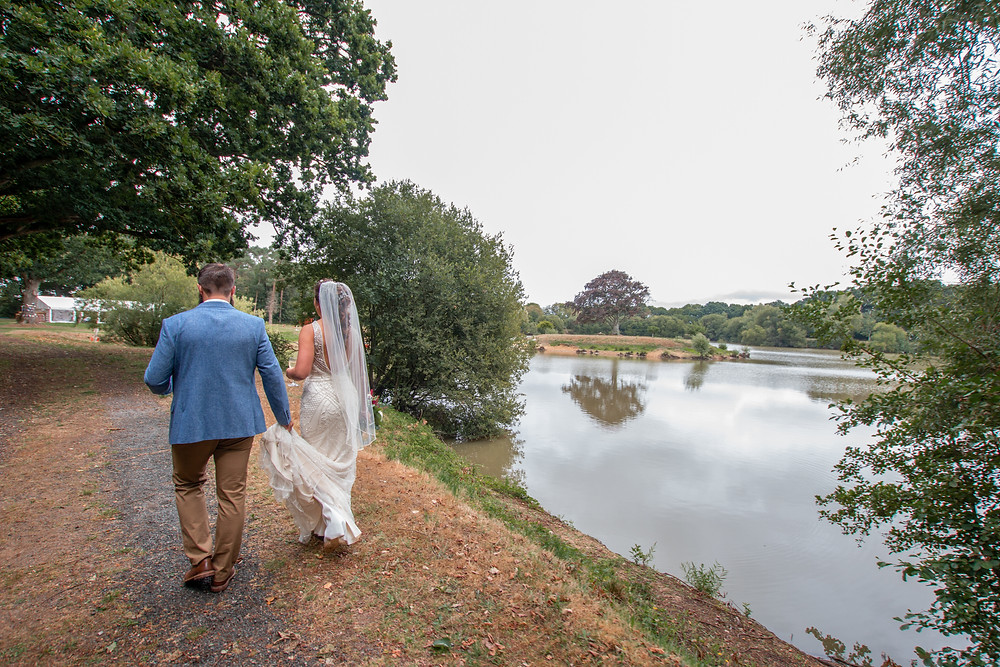 Groom holds brides dress as they walk round lake