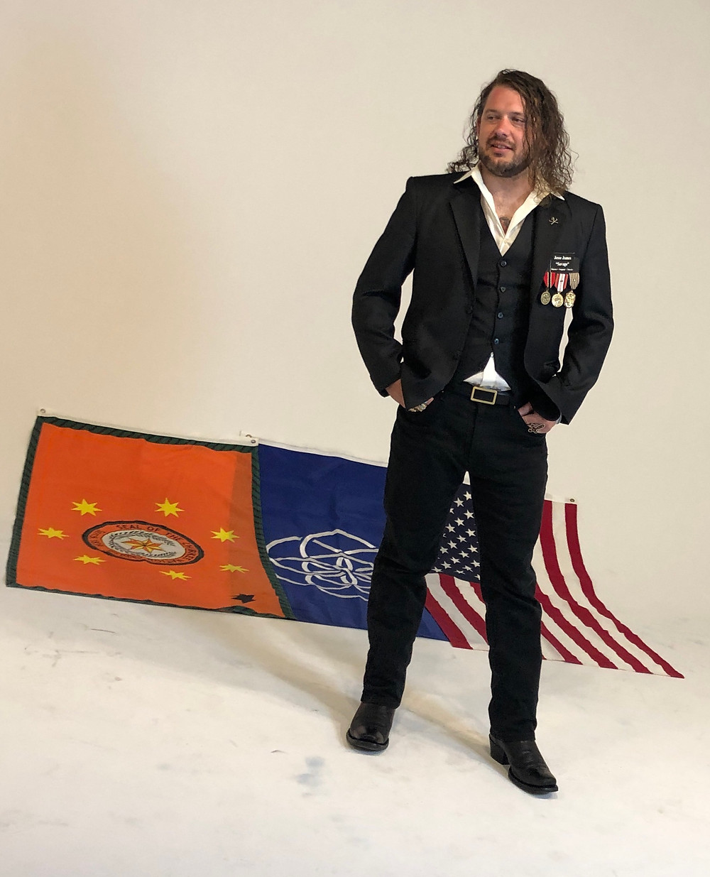 Jesse James Savage standing in front of the Cherokee Nation flag, the proposed world flag, and the U.S. flag.