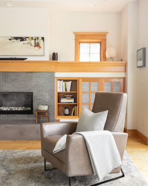 This Craftsman style interior is transformed by applying light wall color, a redesigned fireplace facade, and the addition of contemporary furnishings and art. Integrating mixed materials enhances the beauty of the natural wood elements while creating a uniquely modern aesthetic.
