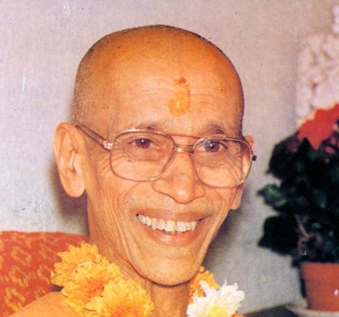 Swami Chidananda lächelnd schaut die Menschen vor einem Vortrag an.