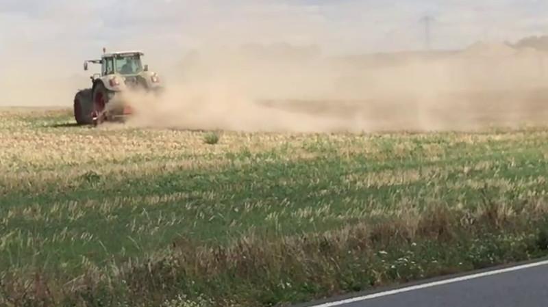 Traktor auf einem Feld erzeugt Humus-Staub - konventionelle Landwirtschaft zerstört den Boden.