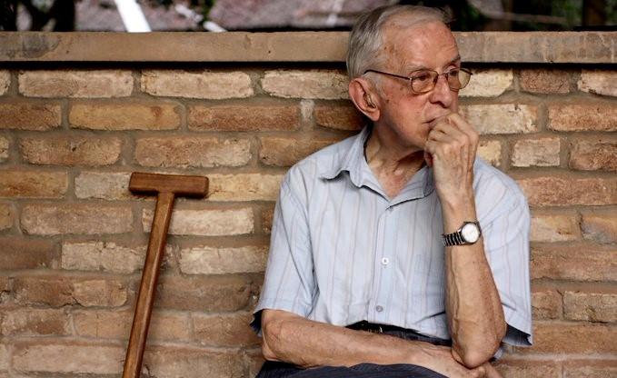 #ParaTodosVerem A imagem é uma foto de D. Pedro Casaldáliga  e  retrata  a parte superior do corpo de  um homem idoso branco de cabelos ralos grisalhos  usando óculos de formato retangular, uma camisa  de mangas curtas azul claro com listras finas e um relógio prateado no pulso esquerdo. D. Pedro tem uma atitude pensativa com a mão esquerda no queixo e está encostado a uma parede de tijolos aparentes. Ao seu lado, uma bengala de madeira.