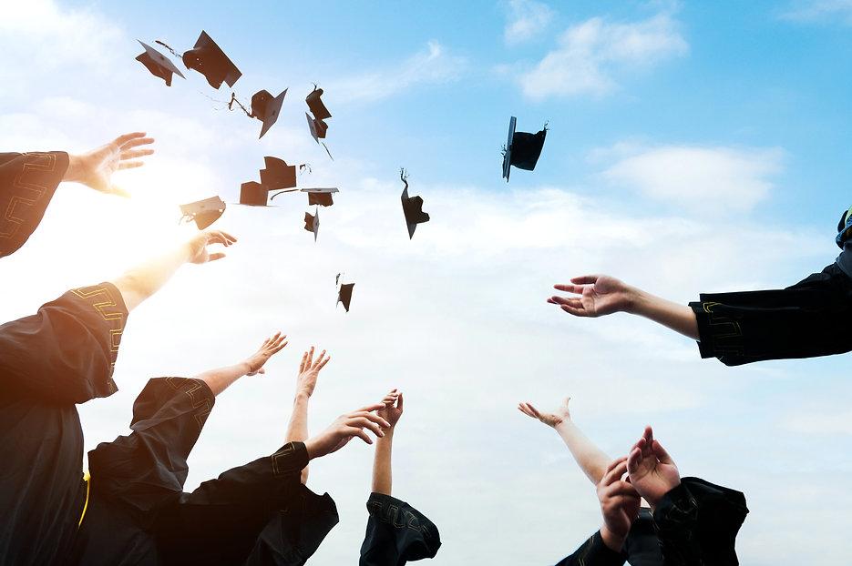 Graduating students hands throwing gradu
