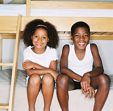 Black boy and girl sit on lower bunk bed