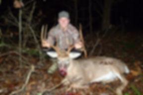 A successful hunter with a huge droptine buck.