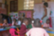 image of a teacher and students in the classroom at circle of peace school