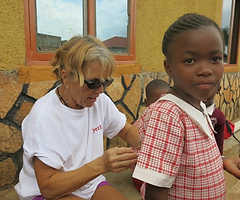 A volunteer sitting with students at Circle of Peace School in Uganda