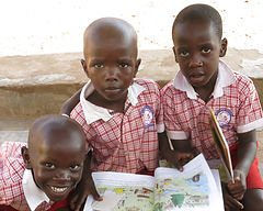 Boy sitting with a book at Circle of Peace School in Uganda