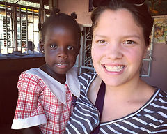 Image of a volunteer holding a student at Circle of Peace School in Uganda