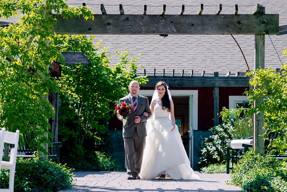 father and bride walk down the aisle