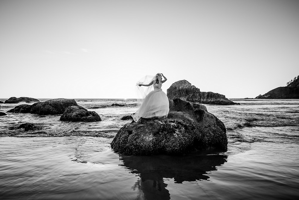 bride on a beach with rocks photo
