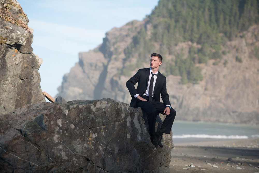 groom sitting on a rock, portrait photography
