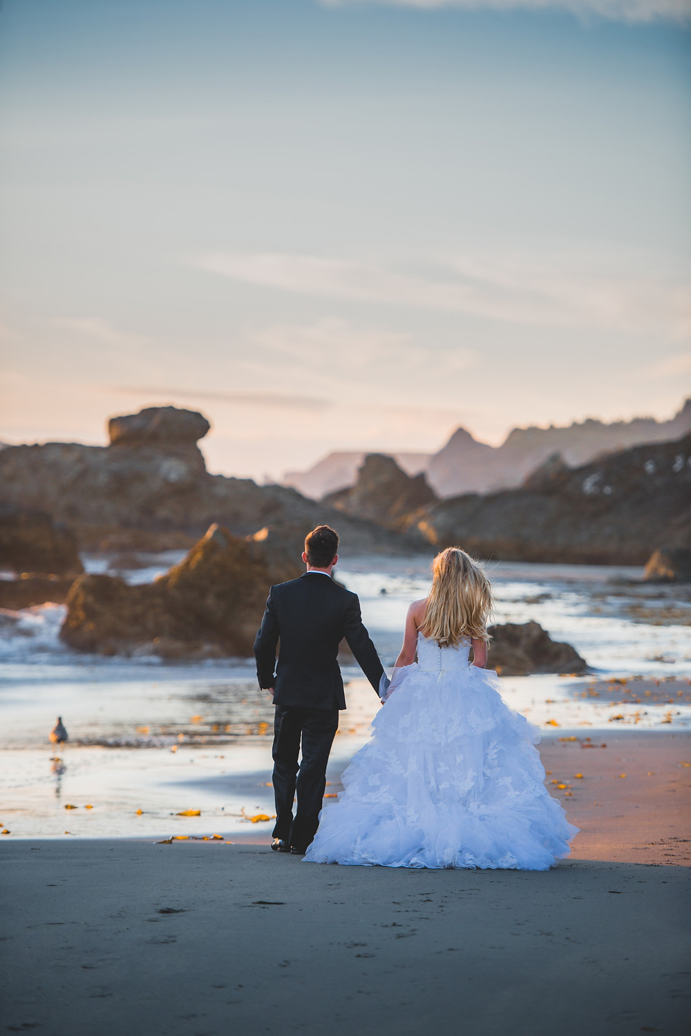 wedding couple walking along the beach at sunset light