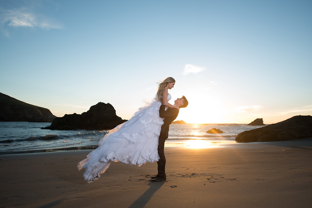 bride and groom dancing at the sunset beach photo