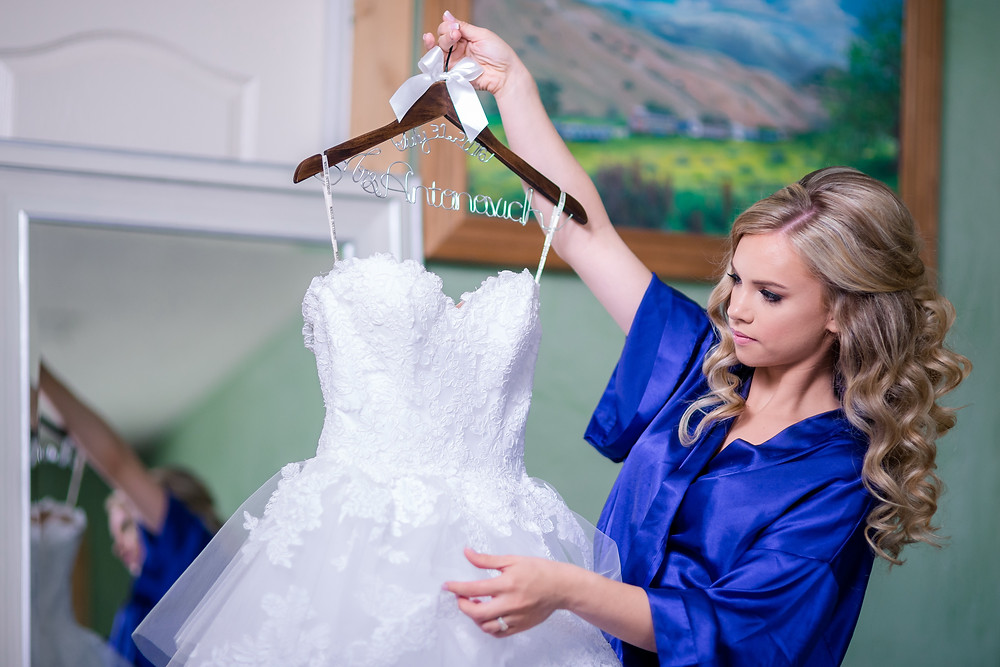 bride hold her wedding dress on a hanger