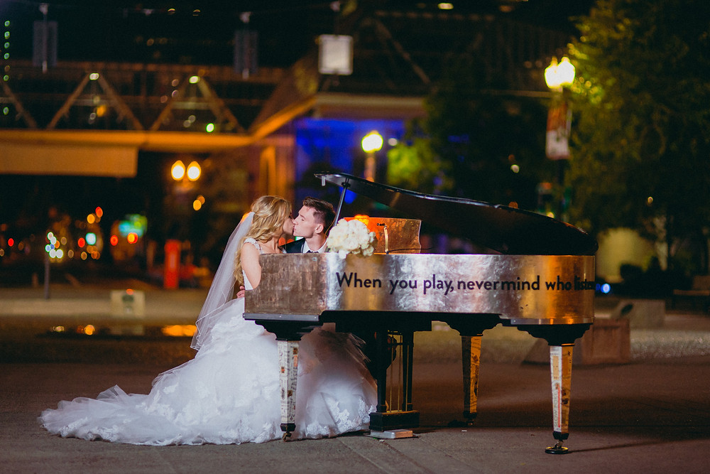 Front Avenue, downtown Portland Oregon, bride and groom kiss at the grand piano