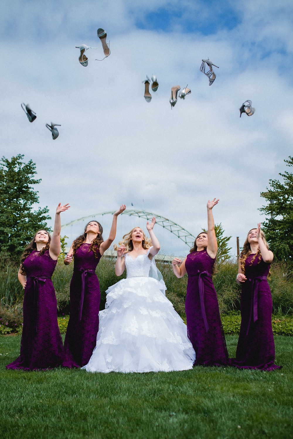 bride and bridesmaid throwing up their shoes