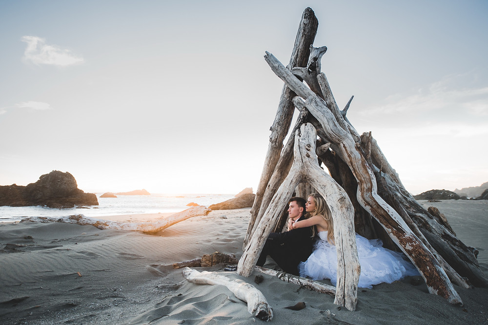 wedding couple on a beach inside a log teepee