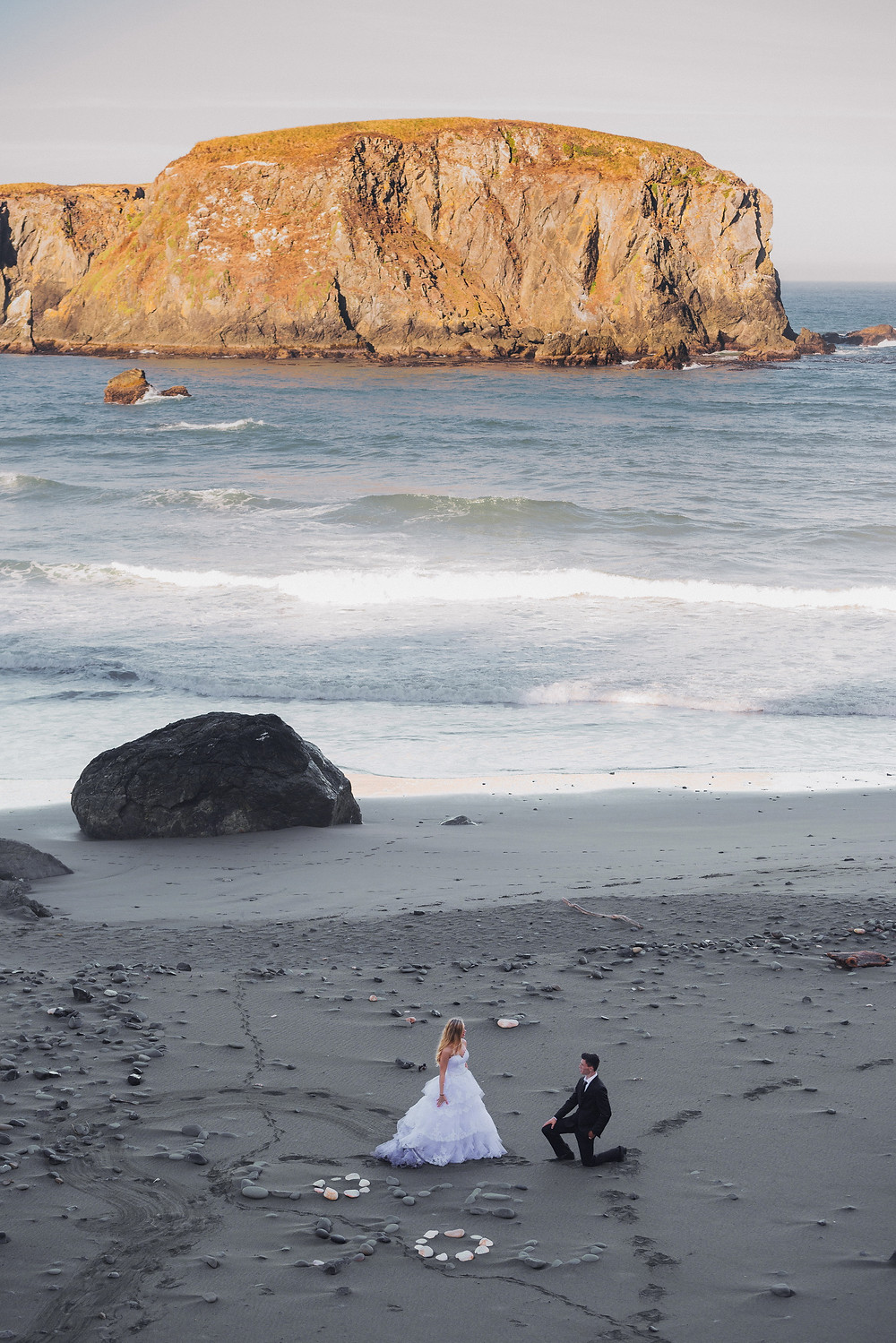 groom on one knee before the bride at the beach photo