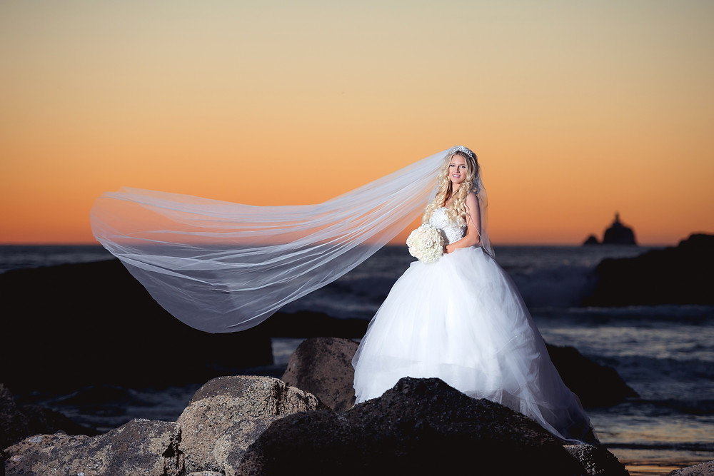 bride with long veil at sunset
