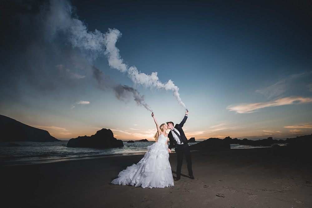 wedding couple kiss with smoke bombs and beautiful landscape view