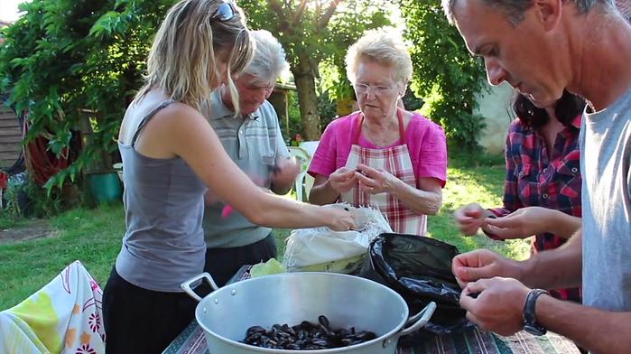 Französische Familie putzt Miesmuscheln für das Familienfest