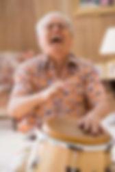 Elderly senior man interacting in a drum circle.