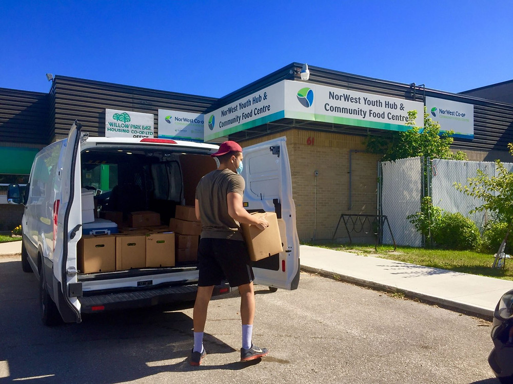 Fireweed Delivery Co-ordinator Conor Nedelec delivers food to the Norwest Co-op Community Food Centre in a Peg City Car Co-op van! Photo by Colby Deighton, courtesy Peg City Car Co-op