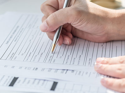 Image of hand filling out form with pen
