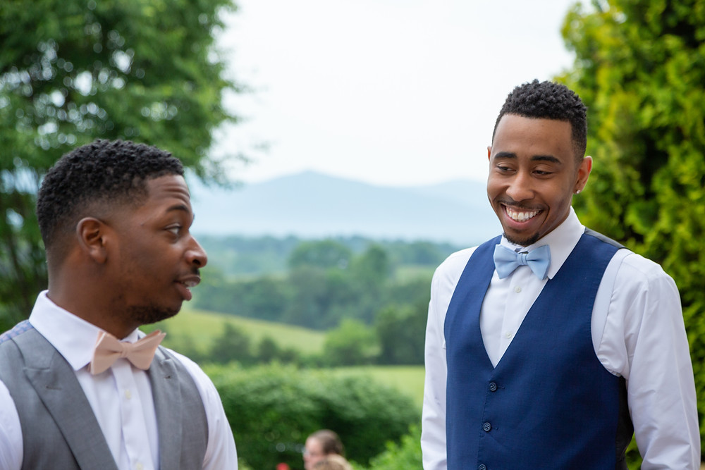 The groom and his best man share a laugh as they approach the alter during the wedding ceremony at Crosskeys Vineyards in Mt. Crawford, Virginia.