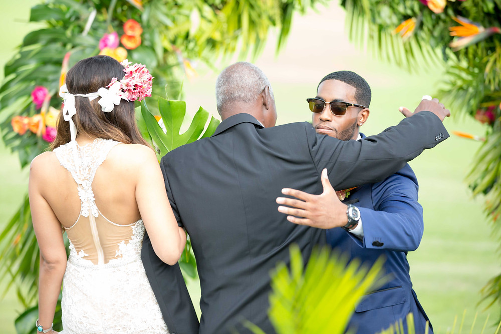 The groom embracing the father-of-the-bride during the destination wedding ceremony.