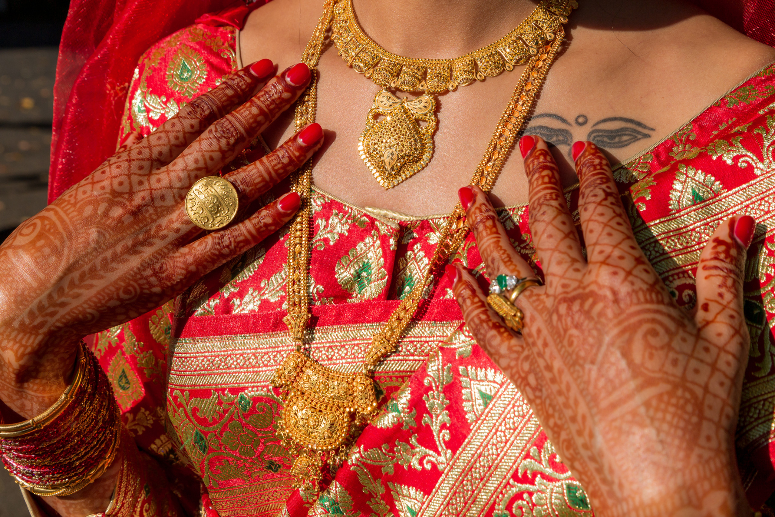 Nepali bride showing off her wedding day henna tattoo, jewelry and ceremonial dress before the Hindu Ceremony at the ISKCON of DC in Potomac, Maryland.