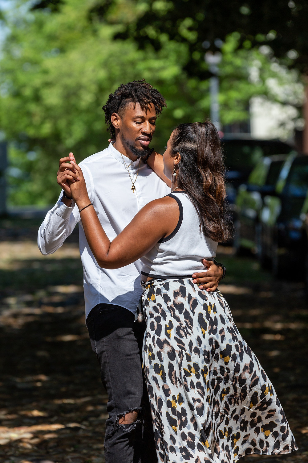 Couple dance on the cobblestone street during their engagement session in Old Town Alexandria, Virginia.