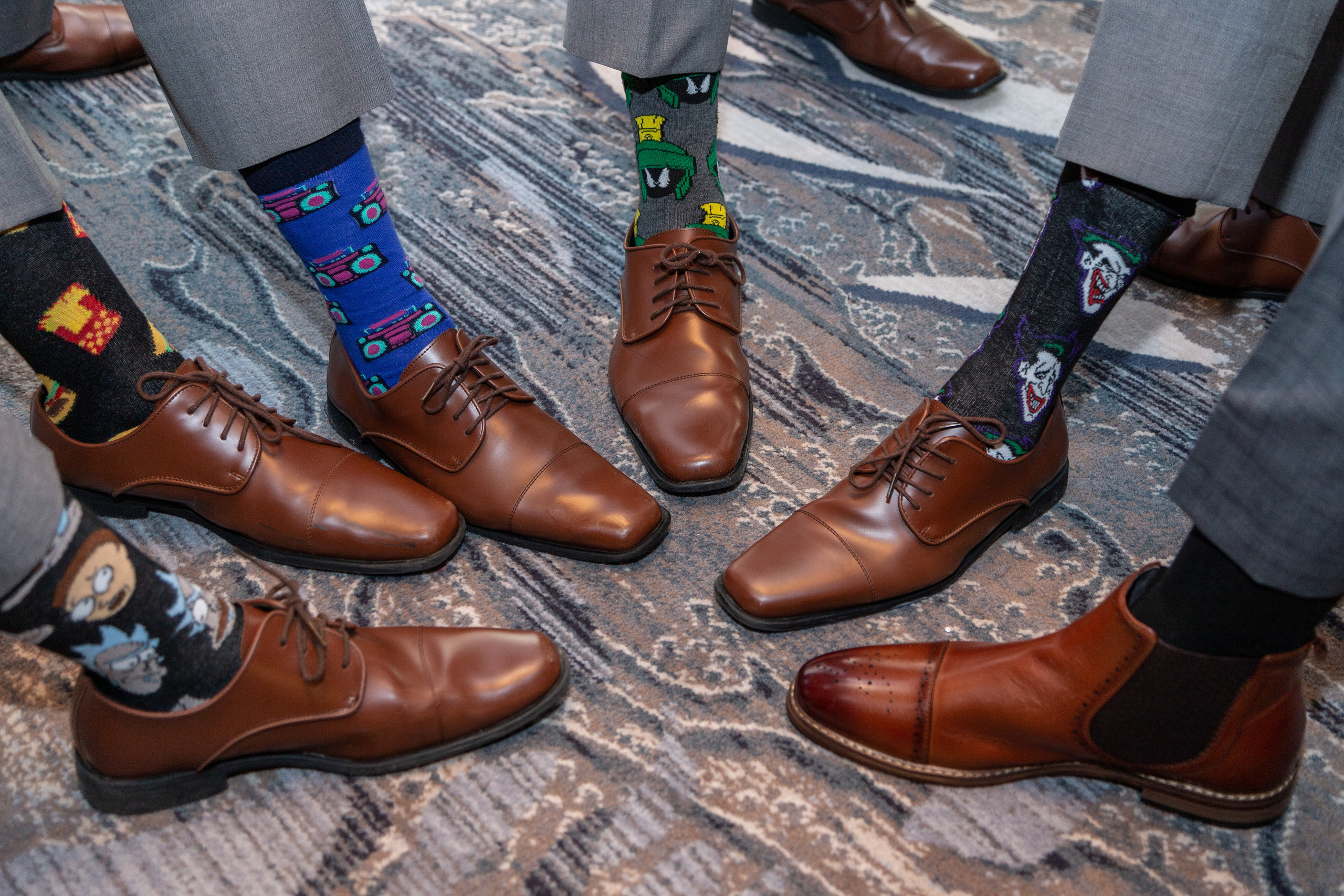 The groom and his groomsmen showing off their fun socks before the wedding at the Hilton Main in Norfolk, Virginia.