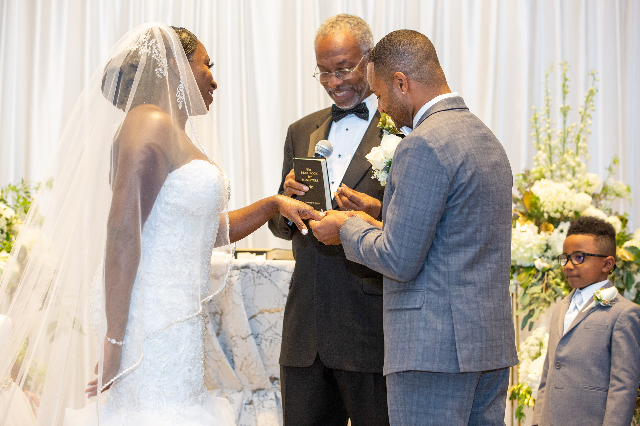 The groom places the bride's wedding band on her hand during the wedding ceremony at the Hilton Main in Norfolk, Virginia.
