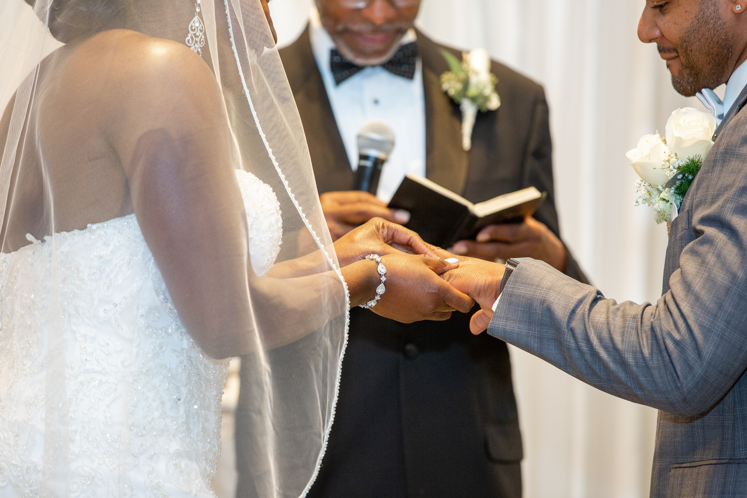 The bride places the groom's wedding band on his hand during the wedding ceremony at the Hilton Main in Norfolk, Virginia.