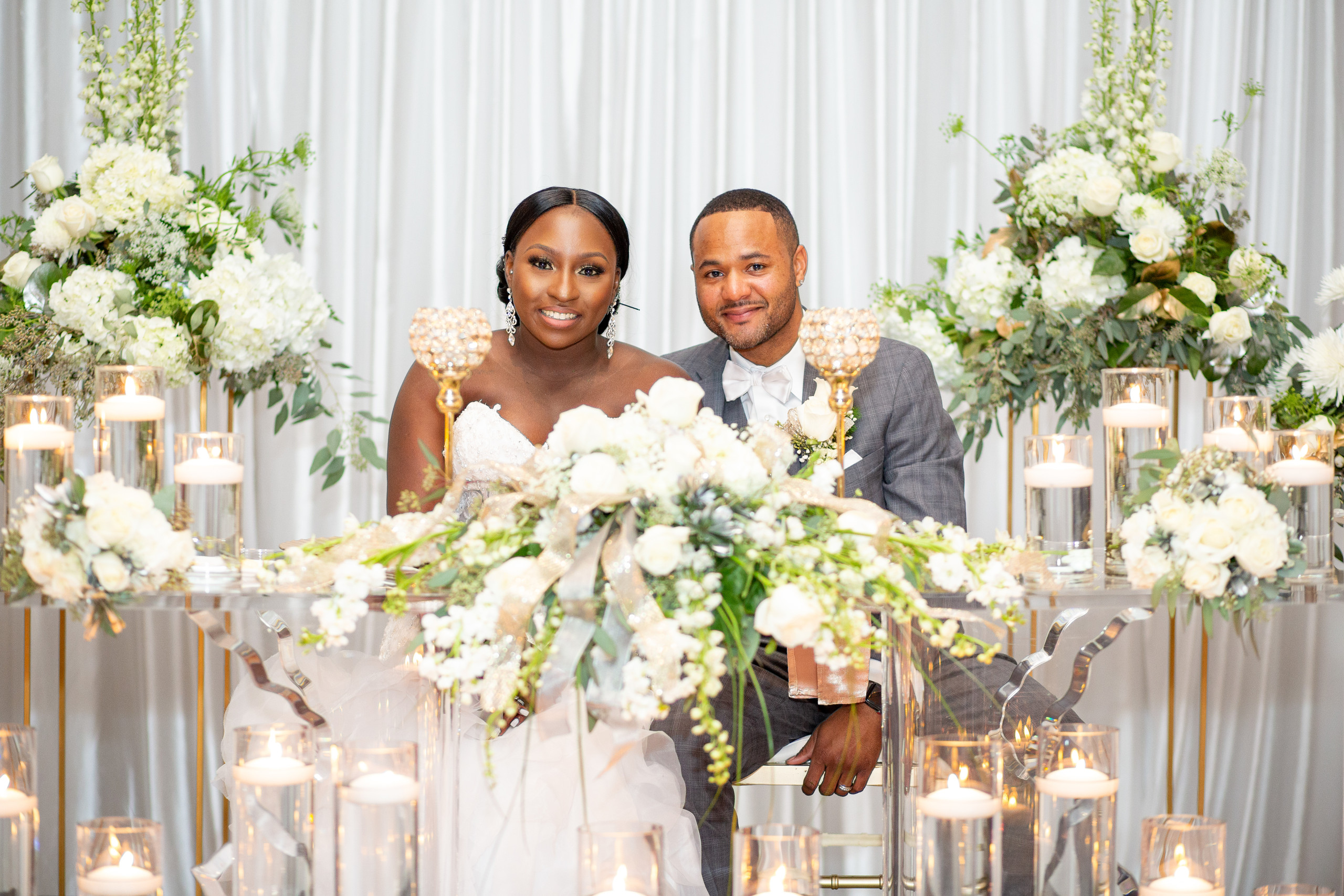 The bride and groom pose at their absolutely stunning couple's table during the wedding reception at the Hilton Main in Norfolk, Virginia.